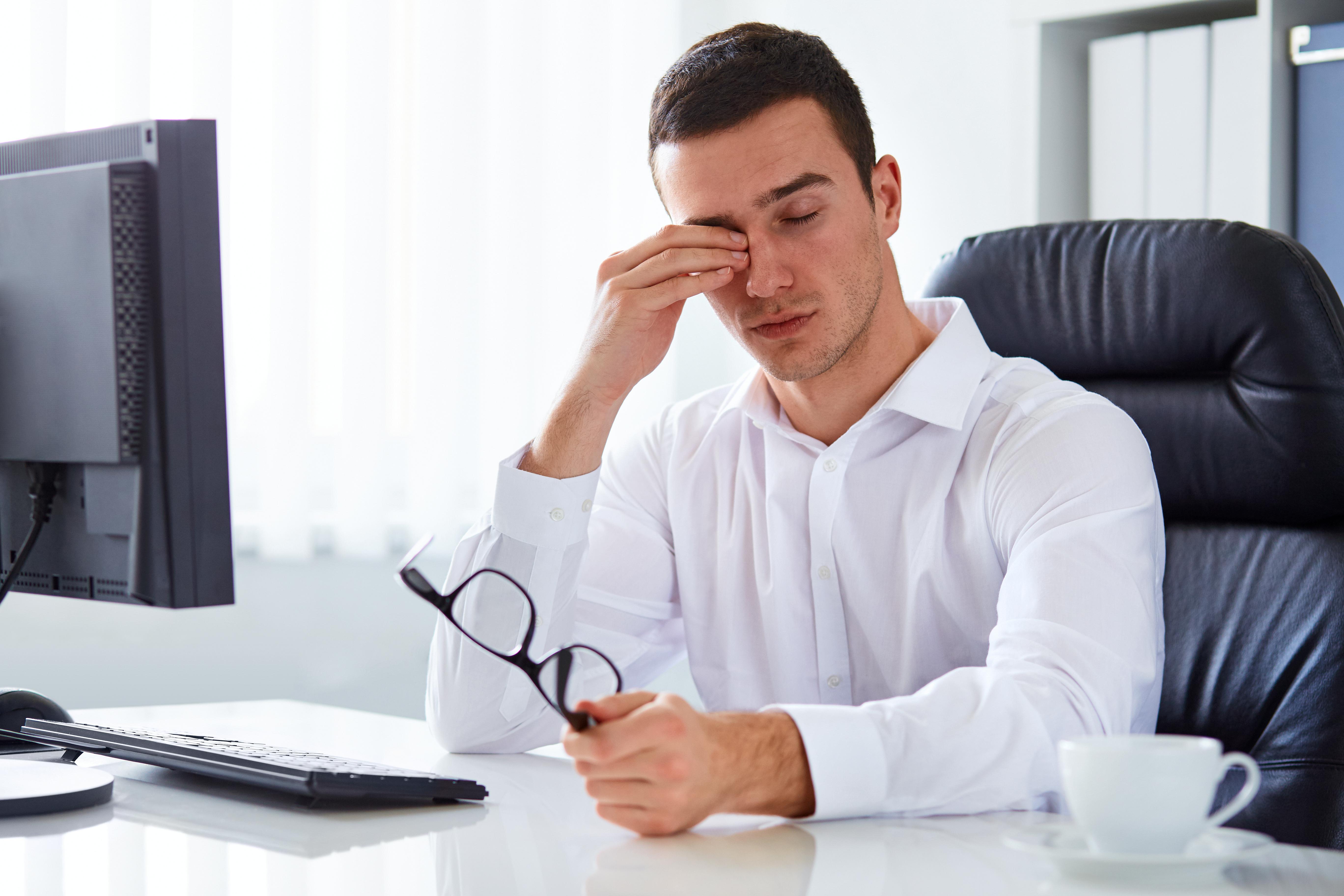man rubbing eyes eye health